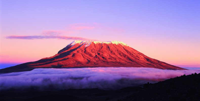 The east side of Mount Kilimanjaro in the morning light, as fog creeps over the Saddle.  The main trekking route can be dimly seen on the left centre of the mountain.